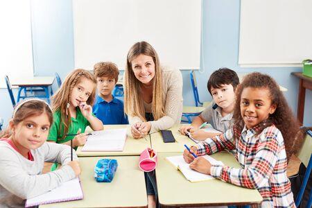Grupa wielokulturowych uczniów szkół podstawowych na lekcjach korepetycji z nauczycielem Zdjęcie Seryjne