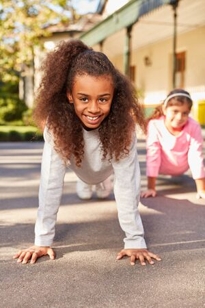 Girl enjoys school physical education and does push-ups