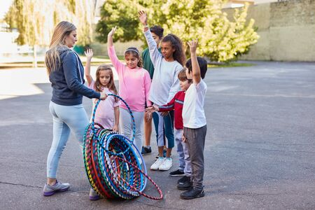 Woman as teacher distributes hoops in physical education to children at summer camp Banco de Imagens