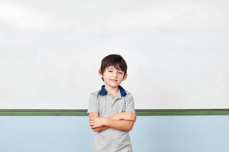 Content student with arms crossed in front of a blackboard in elementary school