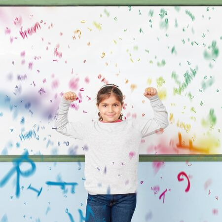 Strong girl stands in elementary school in front of a blackboard with many flying letters