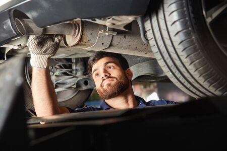 L'ingénieur mécatronique automobile vérifie un échappement pour l'inspection des émissions d'échappement dans l'atelier Banque d'images
