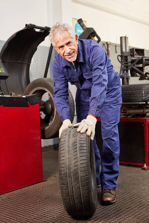 Old mechanic in the workshop with a car tire when changing tires