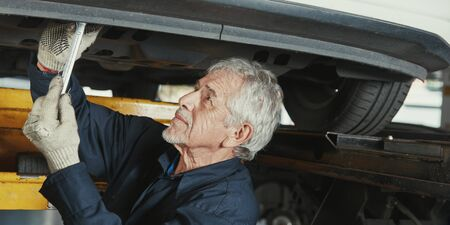 Old car mechanic repairing car in a car workshop