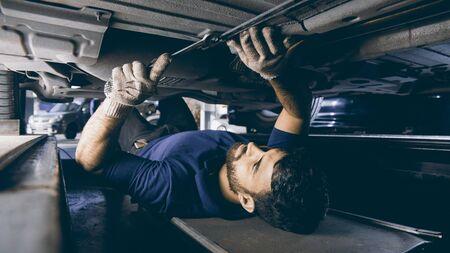 Ingeniero en mecatrónica en Unterboden reparando el automóvil en el taller de automóviles