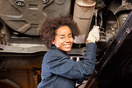 Woman as a mechanic or mechatronics inspecting or repairing under the car