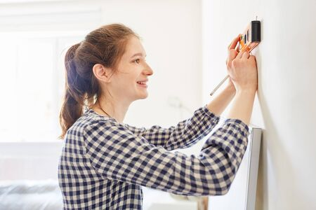 Young woman with pencil and spirit level on the wall while DIY renovating her apartment Stockfoto