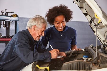 Car Master and African woman as a mechatronics apprentice at the auto inspection 写真素材