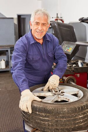 Smiling senior as a competent car mechanic with rim and tires in auto repair shop