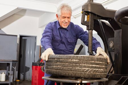 Smiling car mechanic with experience in tire dressing in auto repair shop 写真素材