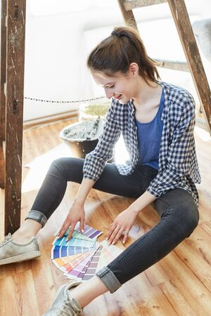 Young handyman sitting on parquet and looking for right wall paint with a color fan