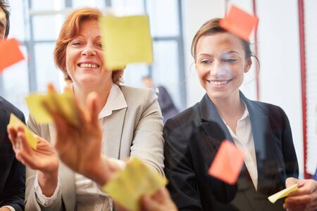Business people put sticky notes on glass in creative workshop
