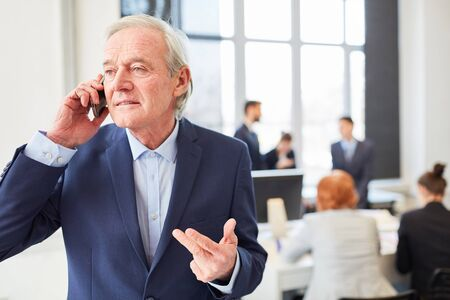 Senior consultant making a business call with smartphone