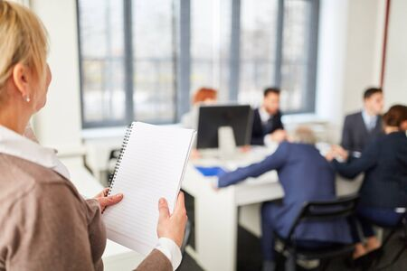 Donna con note in riunione con un gruppo di uomini d'affari