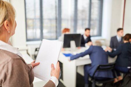 Vrouw met aantekeningen in ontmoeting met een groep zakenmensen