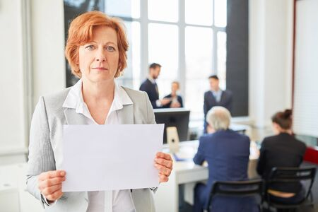 Senior businesswoman holds blank sign in office