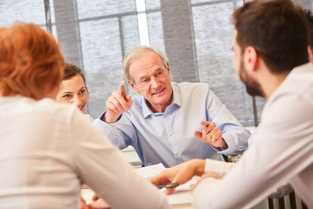 Senior explains business strategy to team in consulting meeting