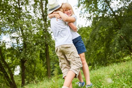 Sibling children greet each other with a hug on a meadow