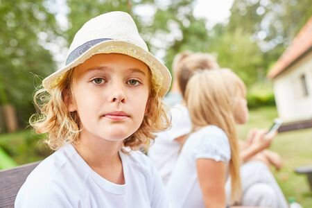 Portrait of a pensive boy with straw hat in the garden during vacations Imagens