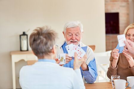 Senior friends playing cards together in the retirement home 写真素材