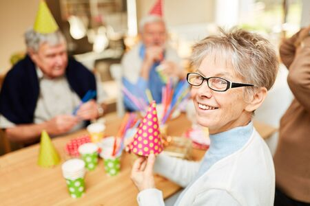 Happy seniors friends celebrate birthday together in retirement home
