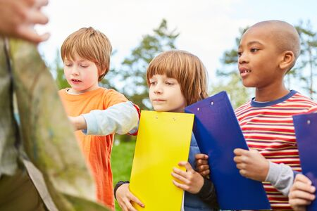 Group of kids with clipboard is doing a field game in elementary or preschool Stock Photo