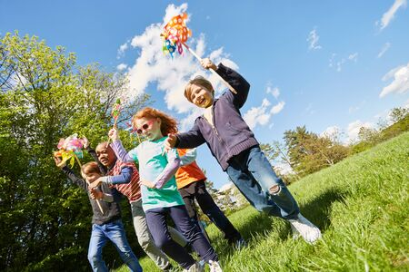 Children have fun at summer camp and run in the sunshine with wind turbines Stock fotó