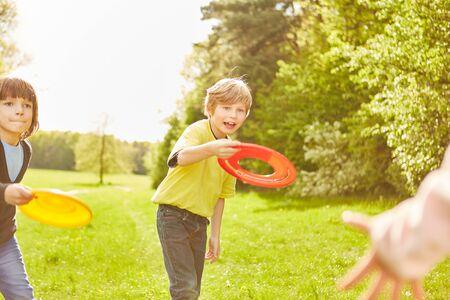 I bambini attivi all'asilo si divertono a giocare a frisbee nel parco in estate Archivio Fotografico