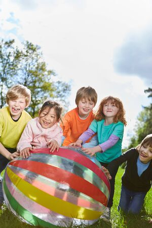 Group of kids together rolls a ball over a meadow at summer camp in summer Stock fotó