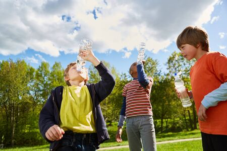Three children in the park are drinking thirstily from water bottles in the summer vacation Reklamní fotografie