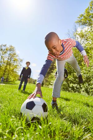 African boy lays down a football for a penalty on the meadow