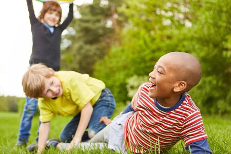 Group of multicultural kids is playing and racking together in the park in summer vacations