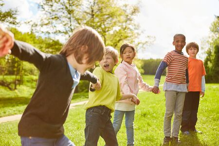 Group of kids holds on to hands in kindergarten or summer camp