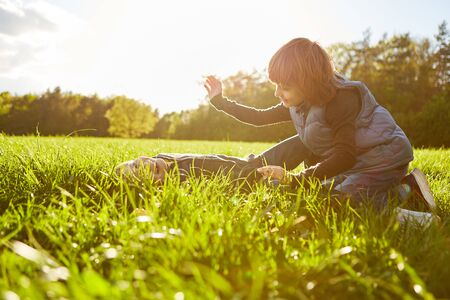 Boy and girl silly laughing around on a summer meadow and tickling each other