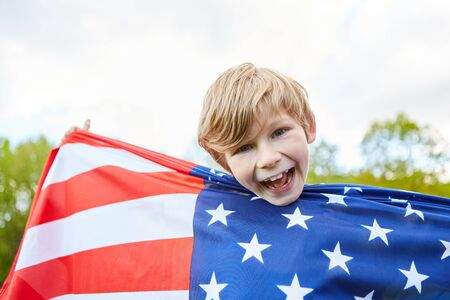 Laughing boy holds the American national flag as a sign of patriotism Stock fotó