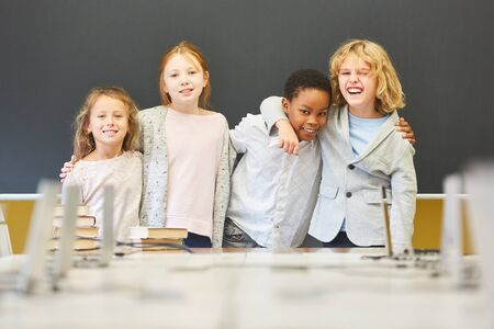 Four children as friends in multicultural elementary school are having fun