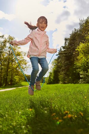 Happy girl in the rope jumping on a meadow in the summer during the holidays Stock fotó
