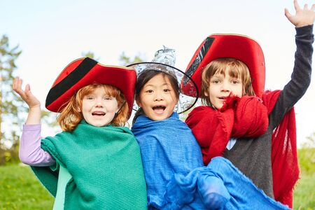 Three children celebrate carnival in colorful costumes or have fun in children's theater