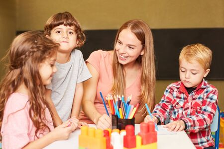 Children and educators have fun together in the painting class of the preschool or kindergarten