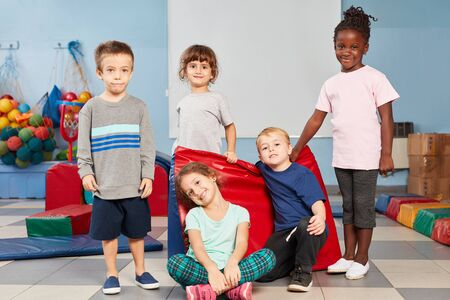 Niños multiculturales como amigos en el gimnasio en jardín de infantes o preescolar.