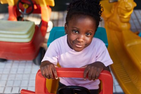African girl in a kindergarten or daycare plays in a pedal car