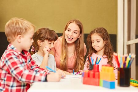 Kindergarten teacher and children in a drawing class in kindergarten or preschool
