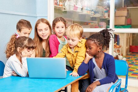 Group of kids and teacher together at laptop in preschool or kindergarten