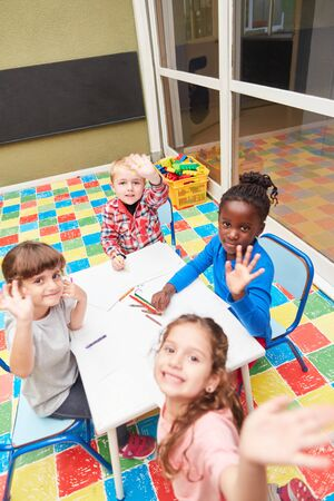 Children as friends in the international kindergarten paint together in the drawing course Banque d'images - 129858162