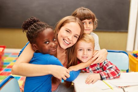 Young woman as a childminder or teacher hugs children in daycare or elementary school Banque d'images - 129858165