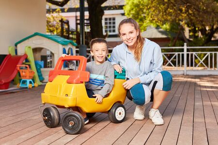 Boy in pedal car and kindergarten teacher have fun together in the garden in kindergarten