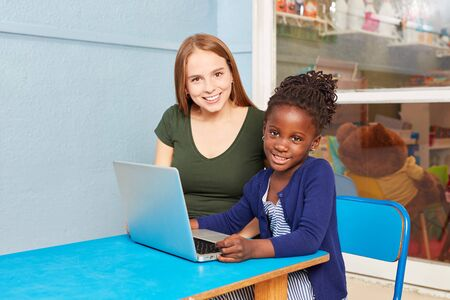 African girl and teacher together learn at laptop PC in kindergarten Фото со стока