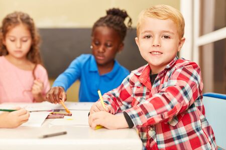 Boy as a pupil or preschooler while painting in painting class in preschool or daycare