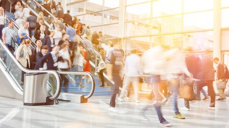 Many business people as a crowd on the escalators of a trade fair Stock Photo