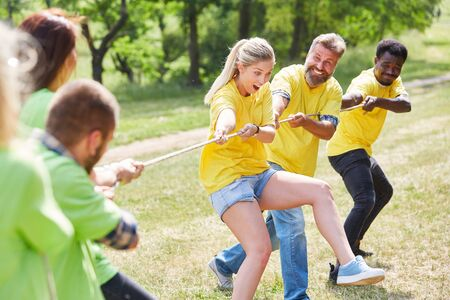 Young team in tug of war as an exercise for team building and team spirit
